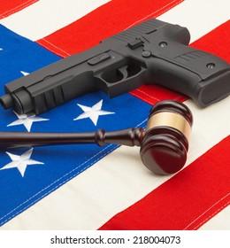 Wooden judge gavel and gun over USA flag - studio shoot - 1 to 1 ratio