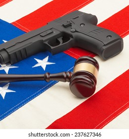 Wooden judge gavel and gun over USA flag - self-defense law concept