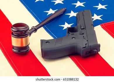 Wooden judge gavel and gun over US flag - studio shot. Filtered image: cross processed vintage effect.