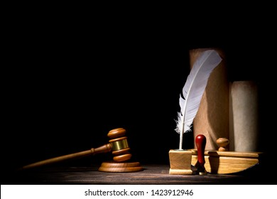 Wooden judge gavel hammer, old inkstand with feather quill, blotter, seal near scrolls against black background. Dramatic light. Vintage still life.