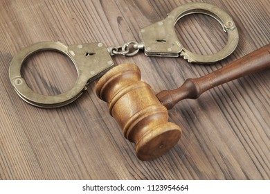 Wooden judge gavel and handcuffs, law and crime concept
