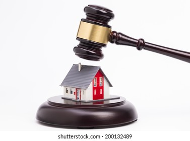 Wooden judge gavel with house isolated on white background