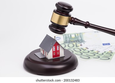Wooden judge gavel with house and money isolated on white background