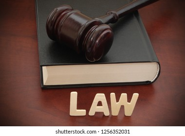 Wooden judge gavel with legal book and word LAW