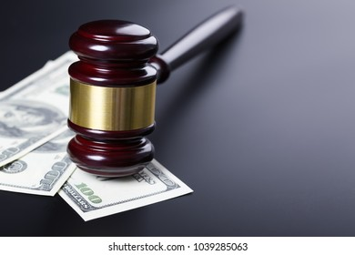 Wooden judge gavel on hundred dollar banknotes closeup over black background