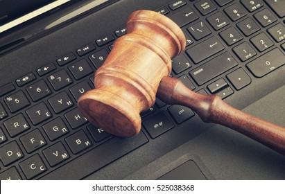 Wooden judge gavel on laptop computer, cyber law or crime concept.