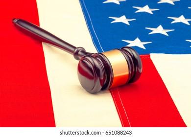 Wooden judge gavel over US flag - closeup studio shot. Filtered image: cross processed vintage effect.