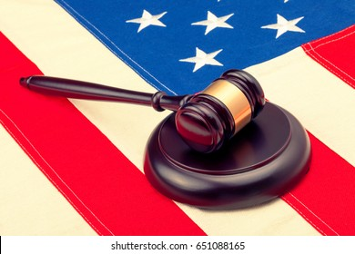 Wooden judge gavel and soundboard laying over USA flag - closeup shot. Filtered image: cross processed vintage effect.