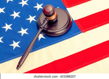 Wooden judge gavel and soundboard laying over US flag. Filtered image: cross processed vintage effect.