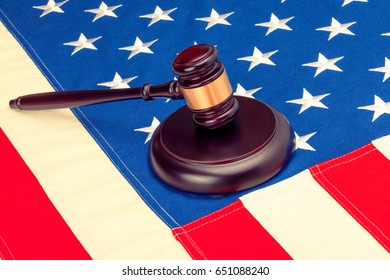 Wooden judge gavel and soundboard laying over US flag - closeup shot. Filtered image: cross processed vintage effect.