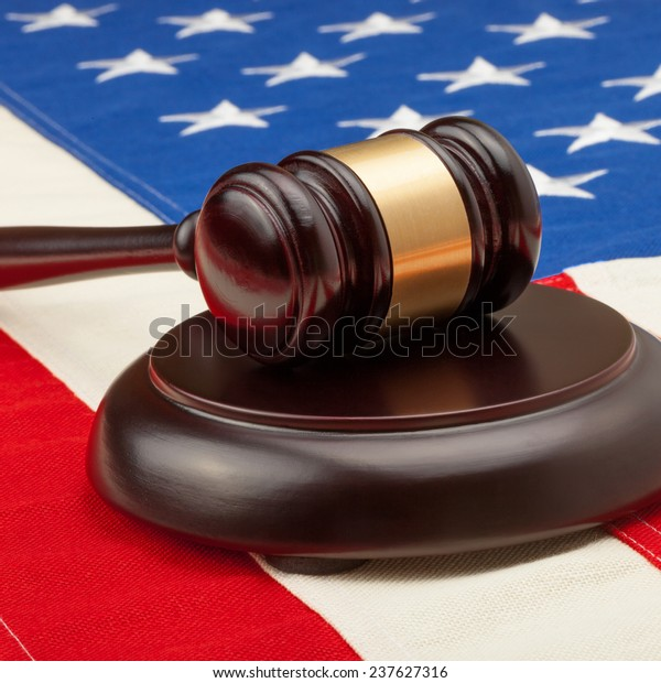 Wooden judge gavel and soundboard laying over USA flag - court judgment concept