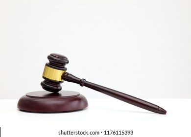 A wooden judge gavel and soundboard on white background.