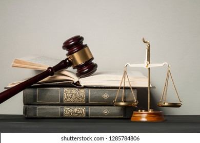 Wooden judge gavel,law scales and stack of books on table in a courtroom.Concept of justice and law.