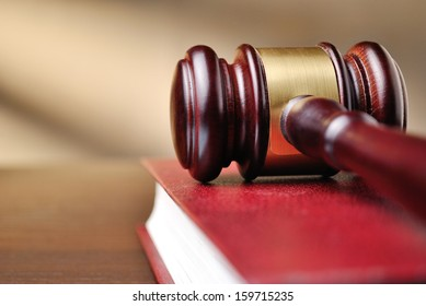 Wooden judges gavel with a brass band around the head resting on top of a closed red law book with shallow dof and copyspace