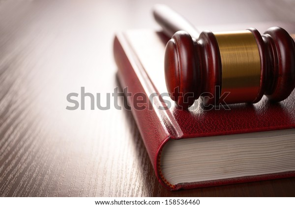 Wooden judges gavel lying on a law book in a courtroom for dispensing justice and sentencing crimes