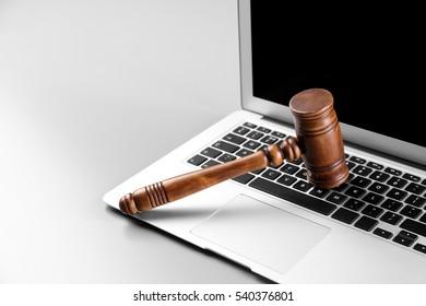Wooden judge's gavel on laptop keyboard, closeup