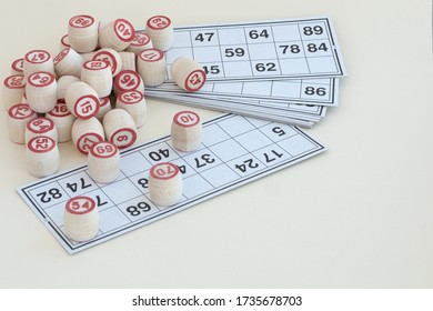 wooden kegs of lotto and cards with digits lie on light background for playing bingo game, family home activities, way to spend time at home, fortune games