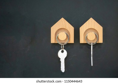 Wooden key hanger against black wall background.