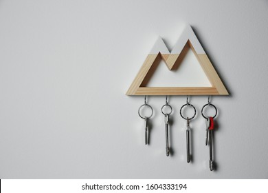 Wooden key holder on light grey wall. Space for text