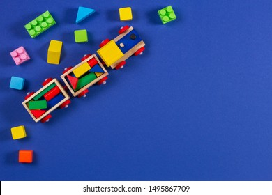Wooden kid toy train with colorful cubes on blue background