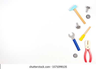 Wooden kids toys screwdriver, plier, bolts, nuts and other construction tools frame on white background. Top view, flat lay
