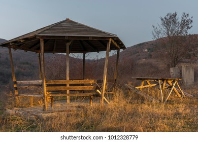 Wooden kiosk with benches in nature