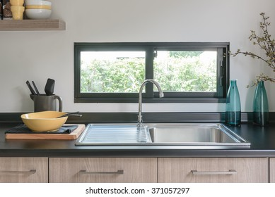 wooden kitchen counter with black granite on top and sink