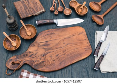 Wooden kitchen cutting Board, wooden kitchen measuring spoons, Damascus kitchen steel Knives. Wooden Cooking utensils background with Santoku damascus steel blade knife