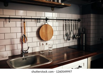 Wooden kitchen design. Loft apartments. Kake slice, ladle, wooden spoon, chopping board and other stuf hang over the table in the kitchen