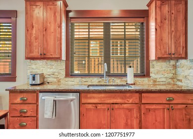 Wooden kitchen room with stone backsplash, granite countertops and stainless steel appliances. Northwest, USA