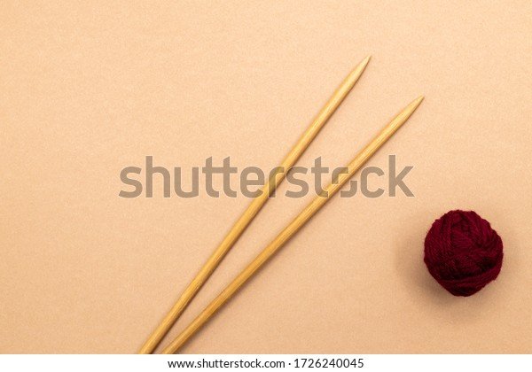 Wooden knitting needles and a ball of red yarn on a beige background with room for copy. Top view.
