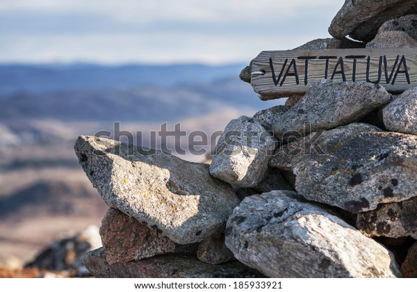 Wooden label on the top of Norwegian mountain with the name of peak