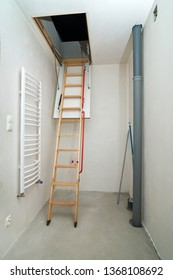 Wooden ladder to attic. Unfinished building interior