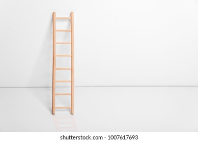 Wooden ladder leaning against the white wall.