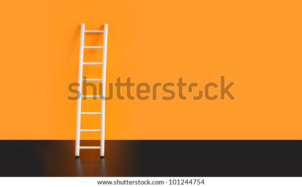 Wooden ladder on black floor against orange wall. Nice background with free space for text