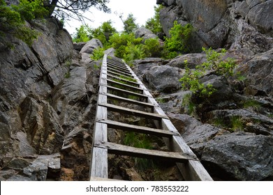 Wooden ladder stretches into the sky, aiding hikers on their climbs up the rocky mountain