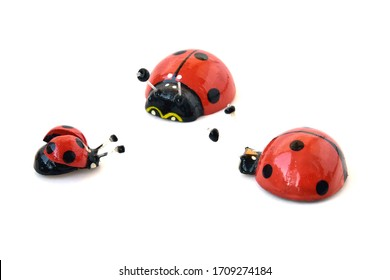Wooden ladybugs on a white background. Three toy insects