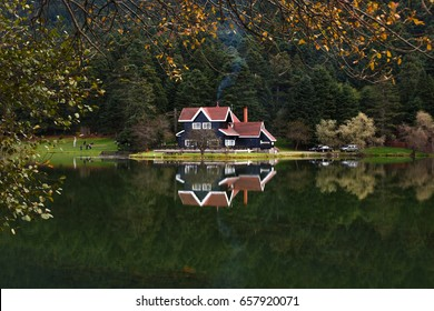 Wooden Lake house inside forest in Bolu Golcuk National Park, Turkey with reflection on the lake on cloudy sky.