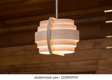 Wooden lamp on a brown background. Modern chandelier of wood in Scandinavian style.