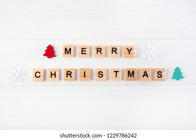 Wooden letters with christmas symbols: snowflakes and trees on white wooden background. Merry christmas greetings.