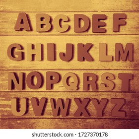 Wooden letters of English alphabet on blue board  background, top view