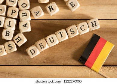 Wooden letters, flag of Italy and the german word for German