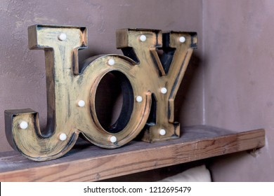 Wooden letters forming word Joy written on grey wall.Christmas postcard. The inscription: Joy to the world. Perfect design for greeting cards,Season of joy.Home decor joy with bulbs on brown