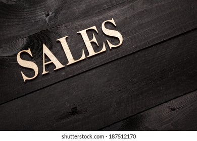 Wooden letters forming word SALES written on black wooden background