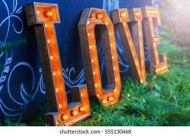 Wooden letters with lights inside. Shining lights in the letters. font. The word love on the grass at the blackboard.