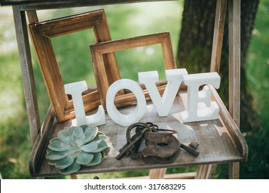 "wooden letters ""LOVE"" are on a wooden shelf in the area for a wedding ceremony"