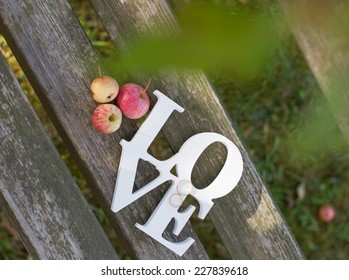 wooden letters love with wedding rings and apples on the bench