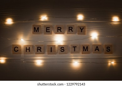 Wooden letters on wooden table with garland. Merry Christmas greetings. Yellow light garland.