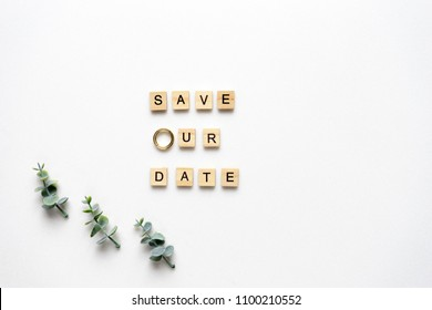 Wooden letters  spelling save our date, oregano branches and wedding rings on white marble. Top view.