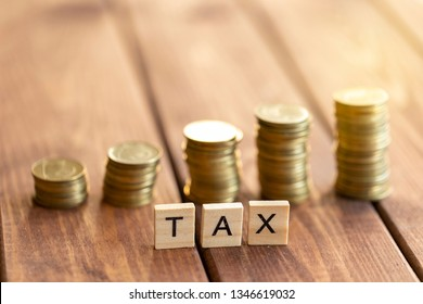 """Wooden letters """"tax"""", coins on the background. Tax obligations concept."""